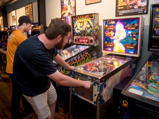 Knoxville News Sentinel writer Ryan Wilusz plays on the Dolly Parton pinball machine at Suttree's High Gravity Tavern.