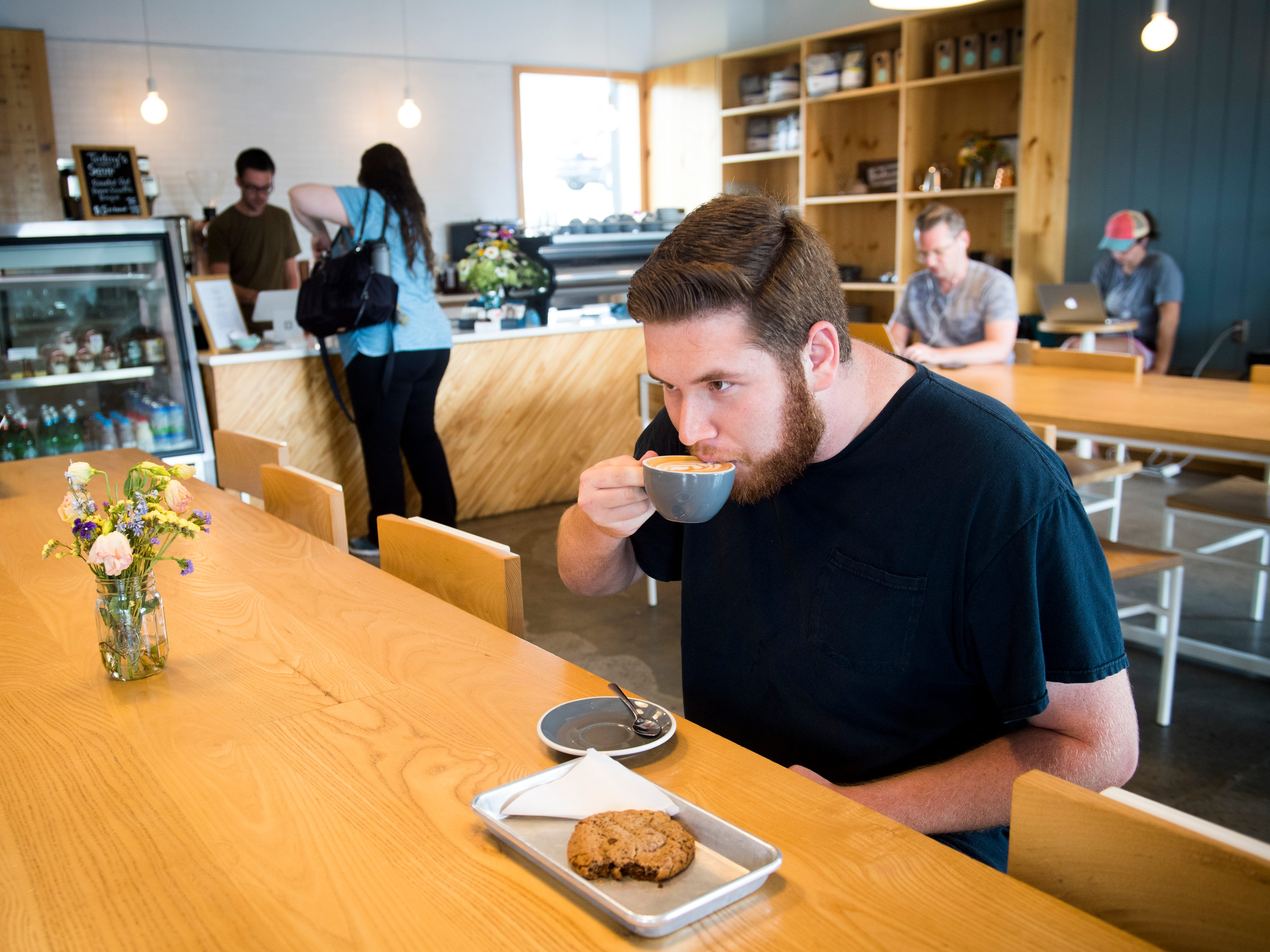 Knoxville News Sentinel urban life writer Ryan Wilusz sips on a cappuccino at Wild Love Bake House on Central as he completes the Knoxville bucket list in one day.
