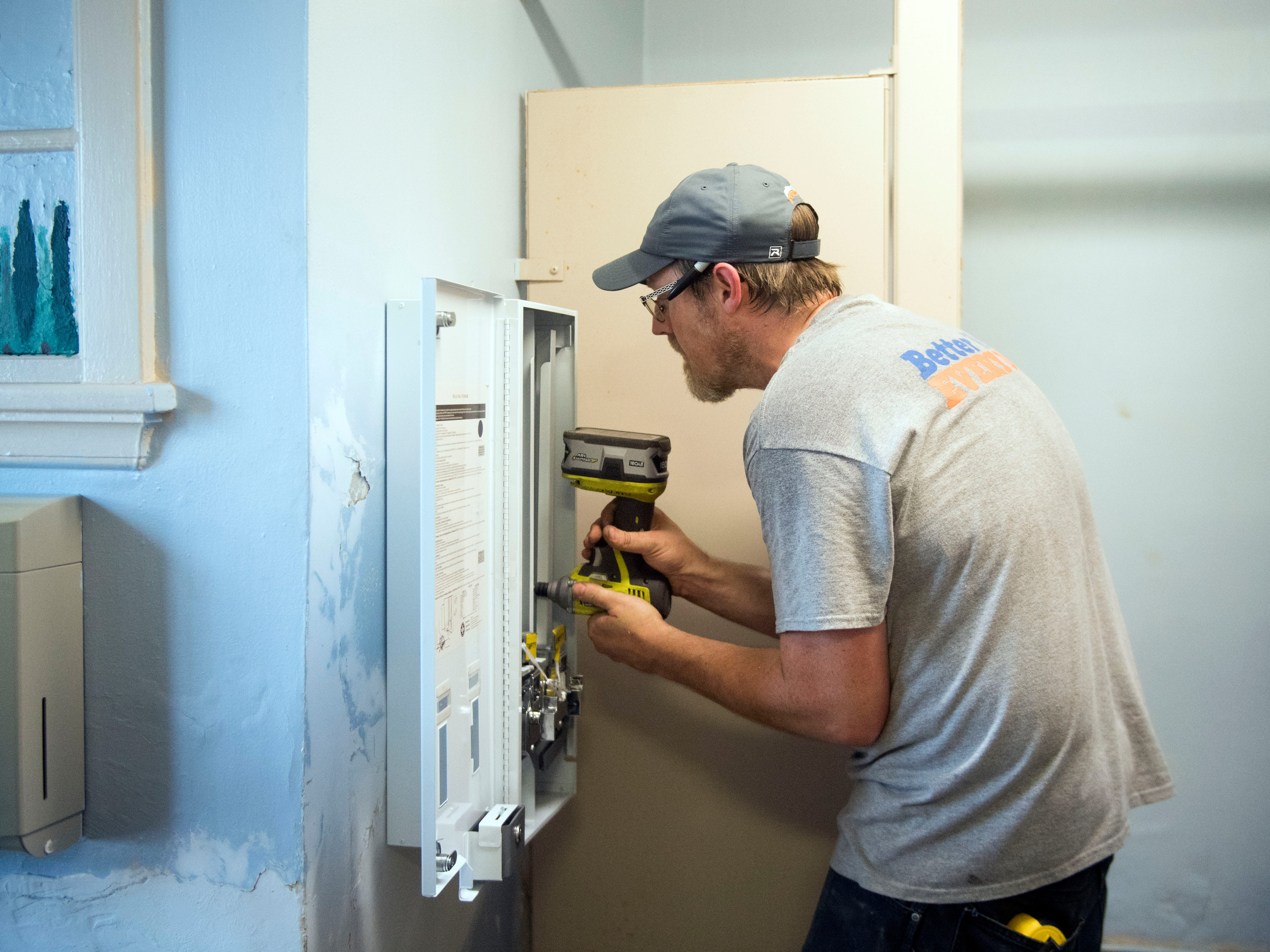 Adam Campbell of Transzonic installs a vending machine that dispenses Maxithin feminine napkins and Tampax Tampons in a bathroom at the YWCA on Wednesday, July 11, 2018. The feminine products are provided freely to residents at the YWCA by Tranzonics, which has a factory in Karns that manufactures and distributes a variety of cleaning, maintenance and personal products.