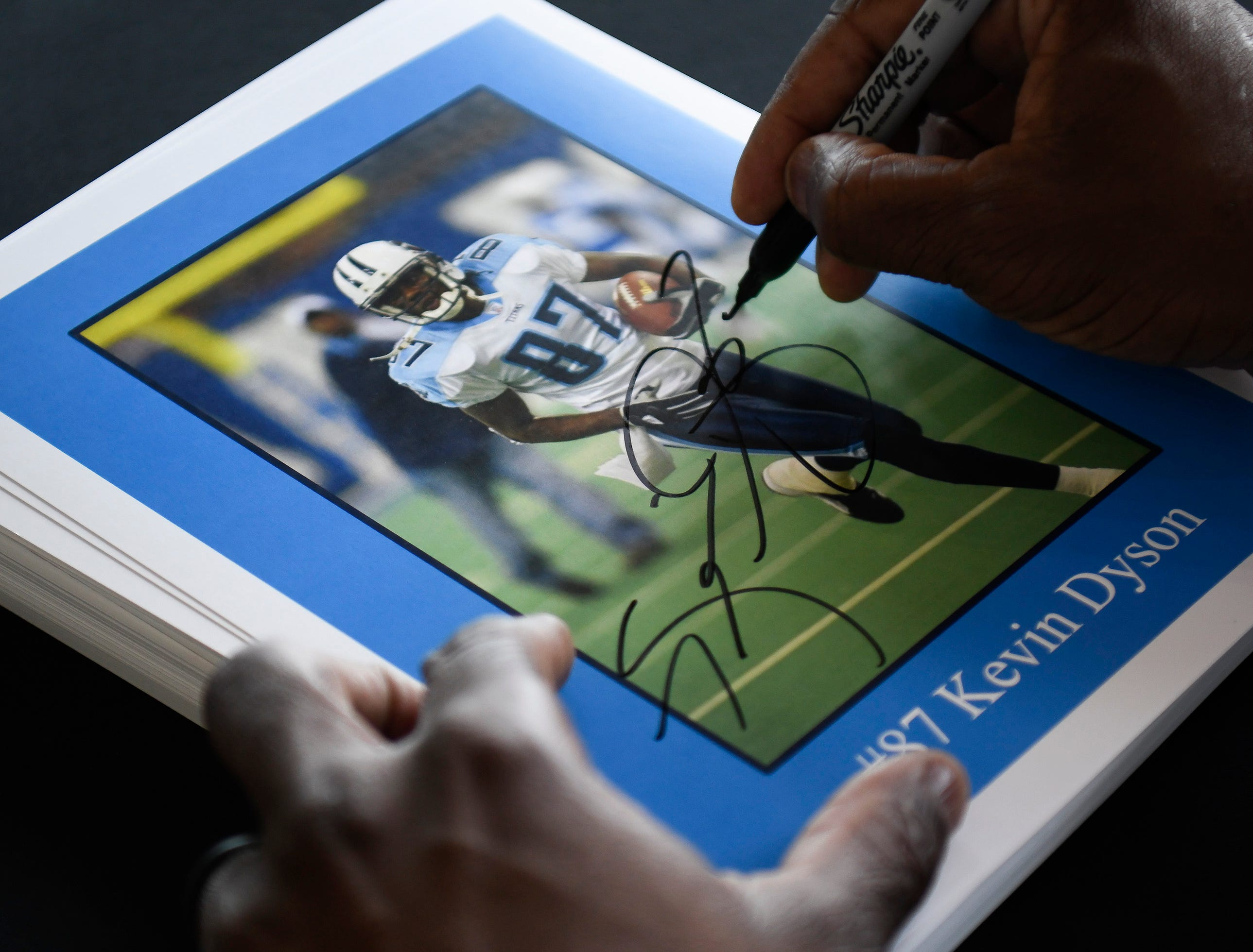 Former Titans wide receiver Kevin Dyson signs autographs for fans during a corporate event at Nissan Stadium Thursday, July 12, 2018, in Nashville, Tenn. Dyson has recently earned his PhD in education from Trevecca University.