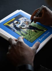 Former Titans wide receiver Kevin Dyson signs autographs for fans during a corporate event at Nissan Stadium on Thursday.