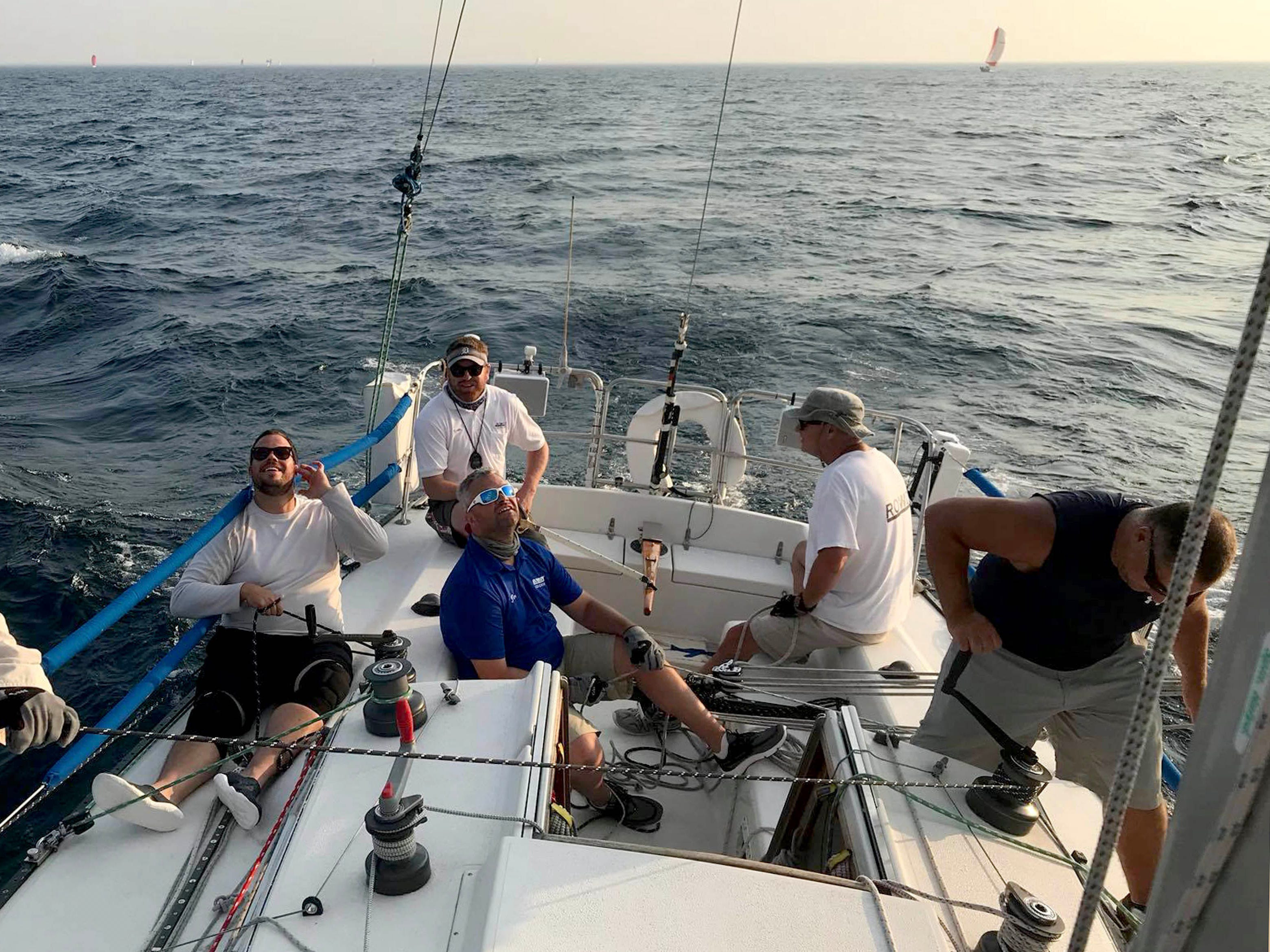 From left, Val Saph Jr. trimming on the winch, Tyson Connolly on the helm, Jim Cole, trimming, Jim Schiller and Jason Mikolayek on the winch on Rowdy, a Thomas 35 sailboat, in Lake Huron during the during the 2017 Port Huron-to-Mackinac race.