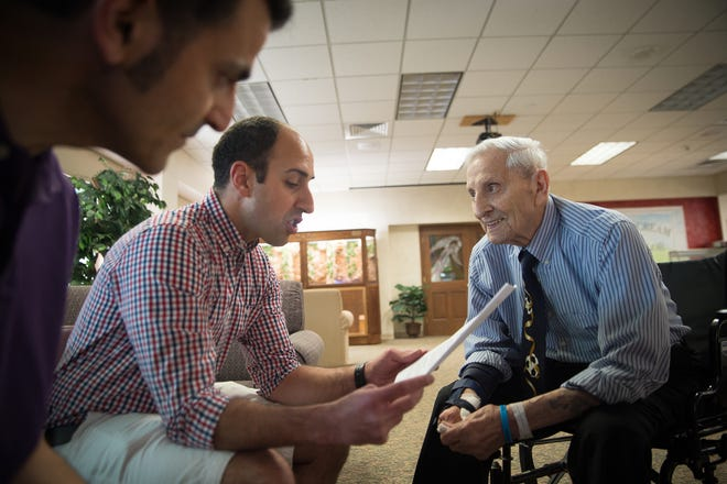 Rick Joseph, left, and Gary Abud, Jr., center, read an article they wrote about their uncle Charles Abud, right, at Shore Pointe Nursing Center in St. Claire Shores on Wednesday, July 11, 2018.