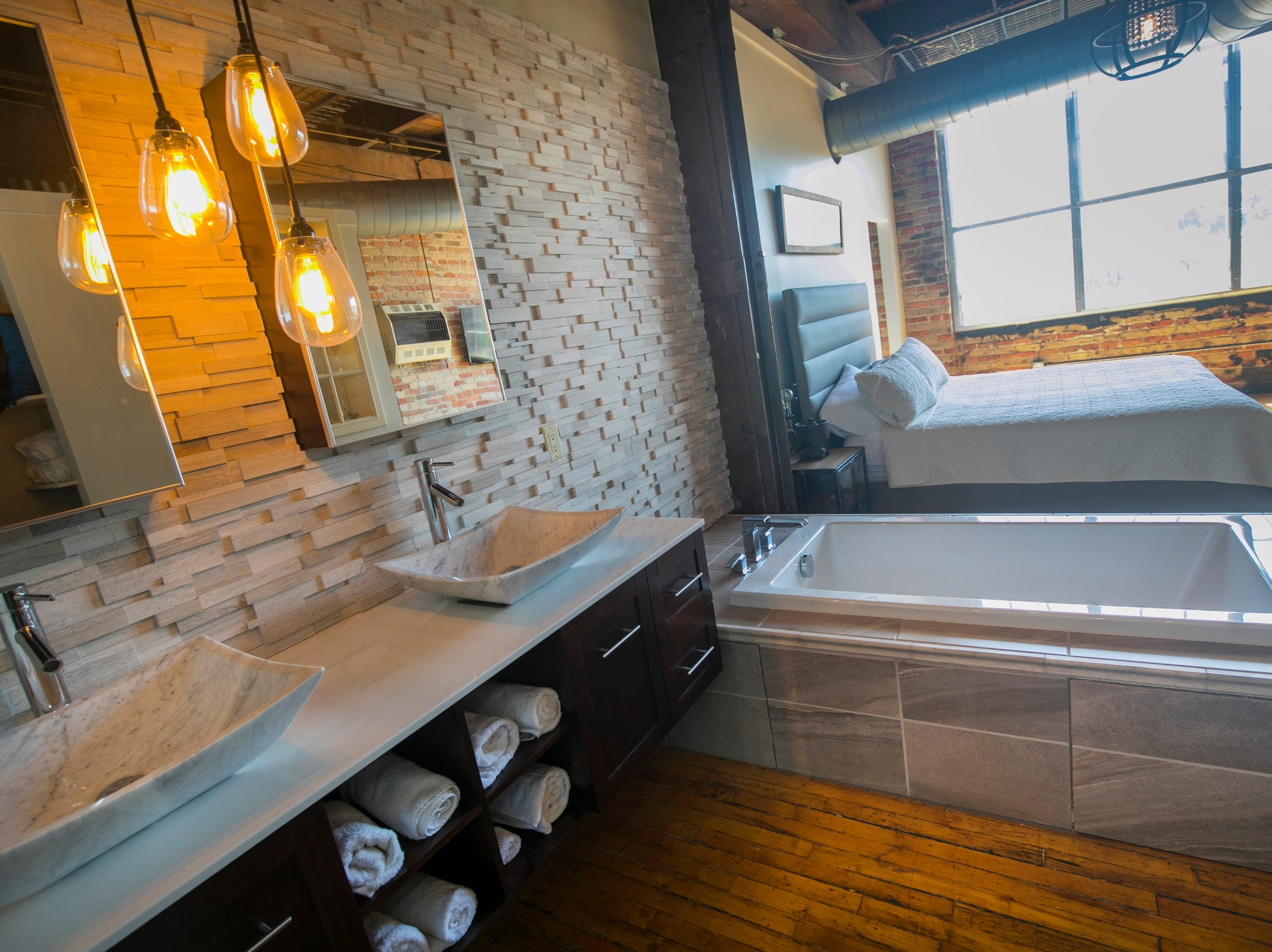 In the large, contemporary owners' suite, the bedroom and bath are combined without walls. There's also a walk-in closet, a wine cooler and a small dishwasher for glasses.