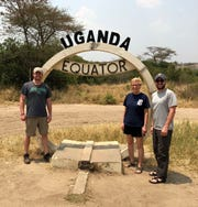 Dr. Andrew Smith of Plymouth, left, Dr. Germaine Fritz of Milford and Dr. Ryan Nielsen of Berkley took the D to  the equator while they were on a medical mission trip to Uganda. All three are orthopedic surgeons who volunteered through Orthopedics Overseas, a division of Health Volunteers Overseas. They spent time teaching doctors in Uganda about orthopedic surgery and working  side by side with them during surgery.