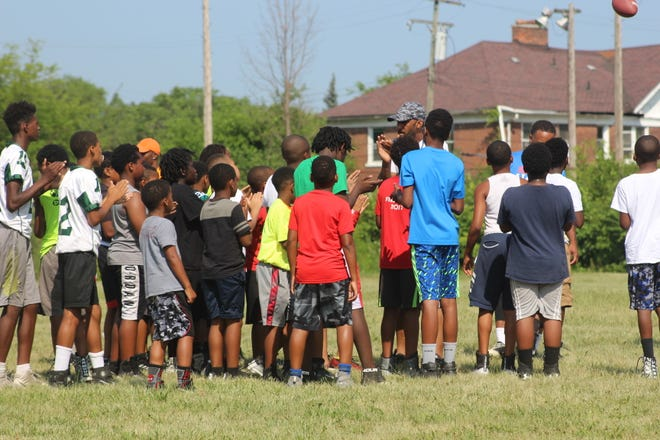 Young football players listen to instruction during the Reggie McKenzie All-Pro Football Clinic on Tuesday, July 10, 2018, in Highland Park.