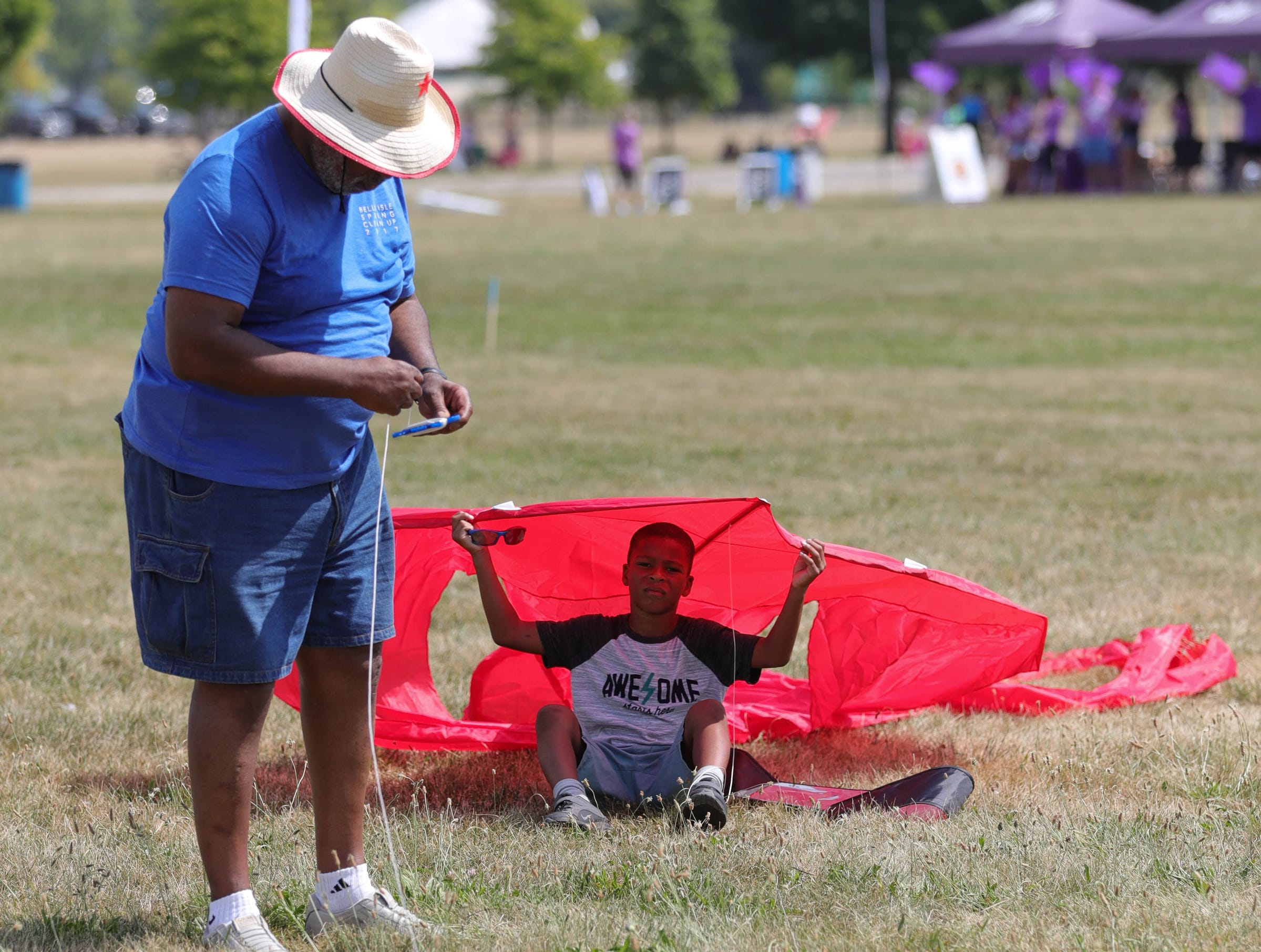 Ethan Vinson and his grandson Ethan Vinson, 6, work on their kite during the Detroit Kite Festival on Belle Isle Sunday, July 15, 2018. Kite enthusiasts from all over Metro Detroit enjoyed the free festivities which included on-site kite making with the Detroit Institute of Arts and professional kite flyers.