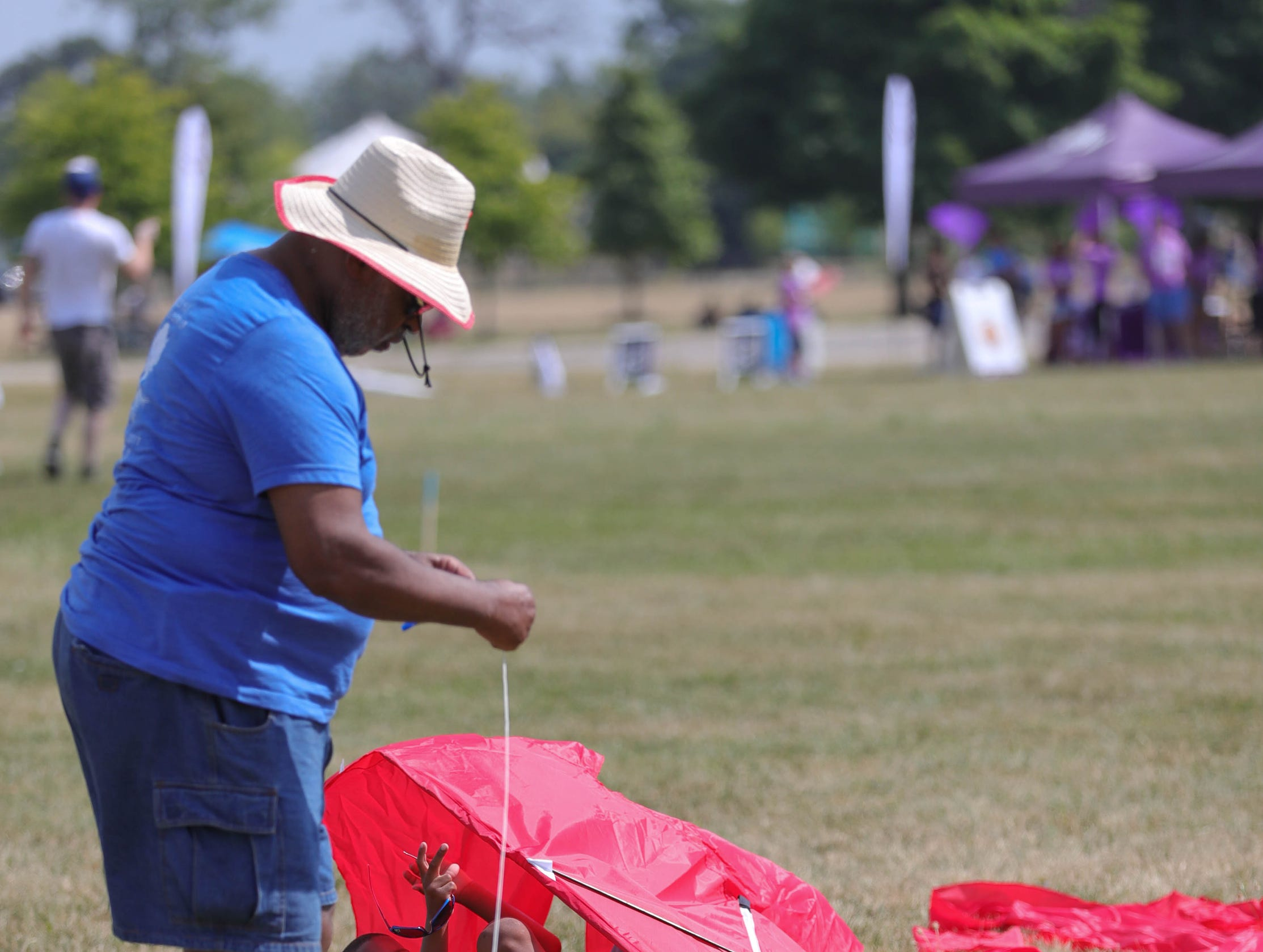 Ethan Vinson and his grandson Ethan Vinson 6, work on their kite during the Detroit Kite Festival on Belle Isle Sunday, July 15, 2018. Kite enthusiasts from all over Metro Detroit enjoyed the festivities.