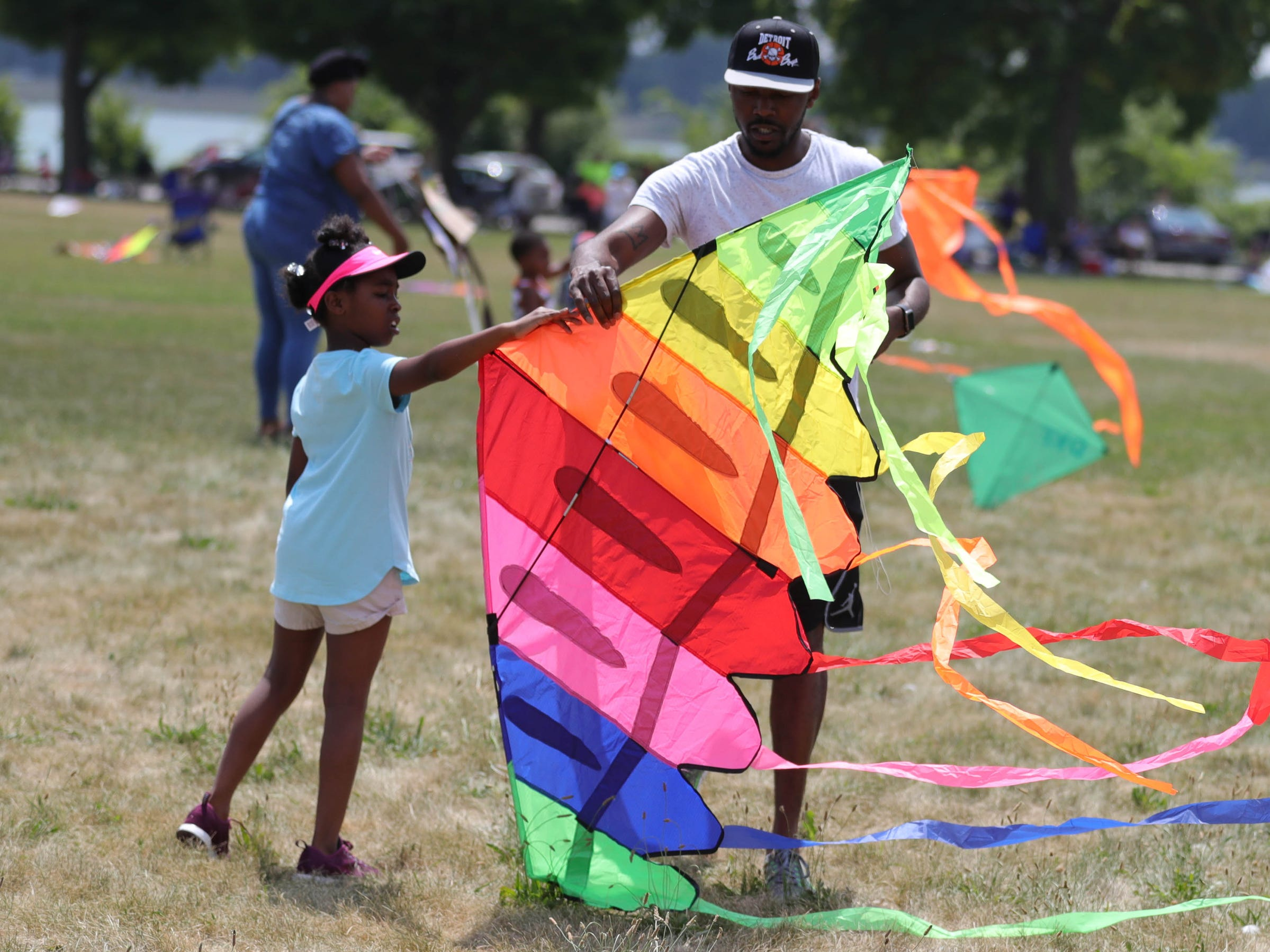 Cortez Settles and his daughter Linda Settles, 7, work on their kite during the Detroit Kite Festival on Belle Isle Sunday, July 15, 2018.