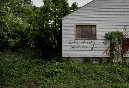"""An abandoned home is spray painted with the words """"City must demolish!,"""" on the corner of Curtis and Biltmore streets on the west side of Detroit on Monday, July 16, 2018."""