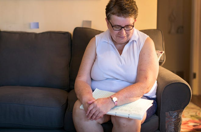 Barbara Yokom, 64, looks at the ledger she has of medical costs, in Redford, Monday, July 17, 2018.