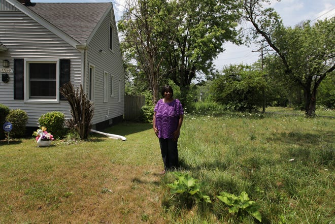 Hattie Smith, 72 wishes that the city of Detroit would cut the grass more often on the lot next to her property on the west side of Detroit on Monday, July 16, 2018.