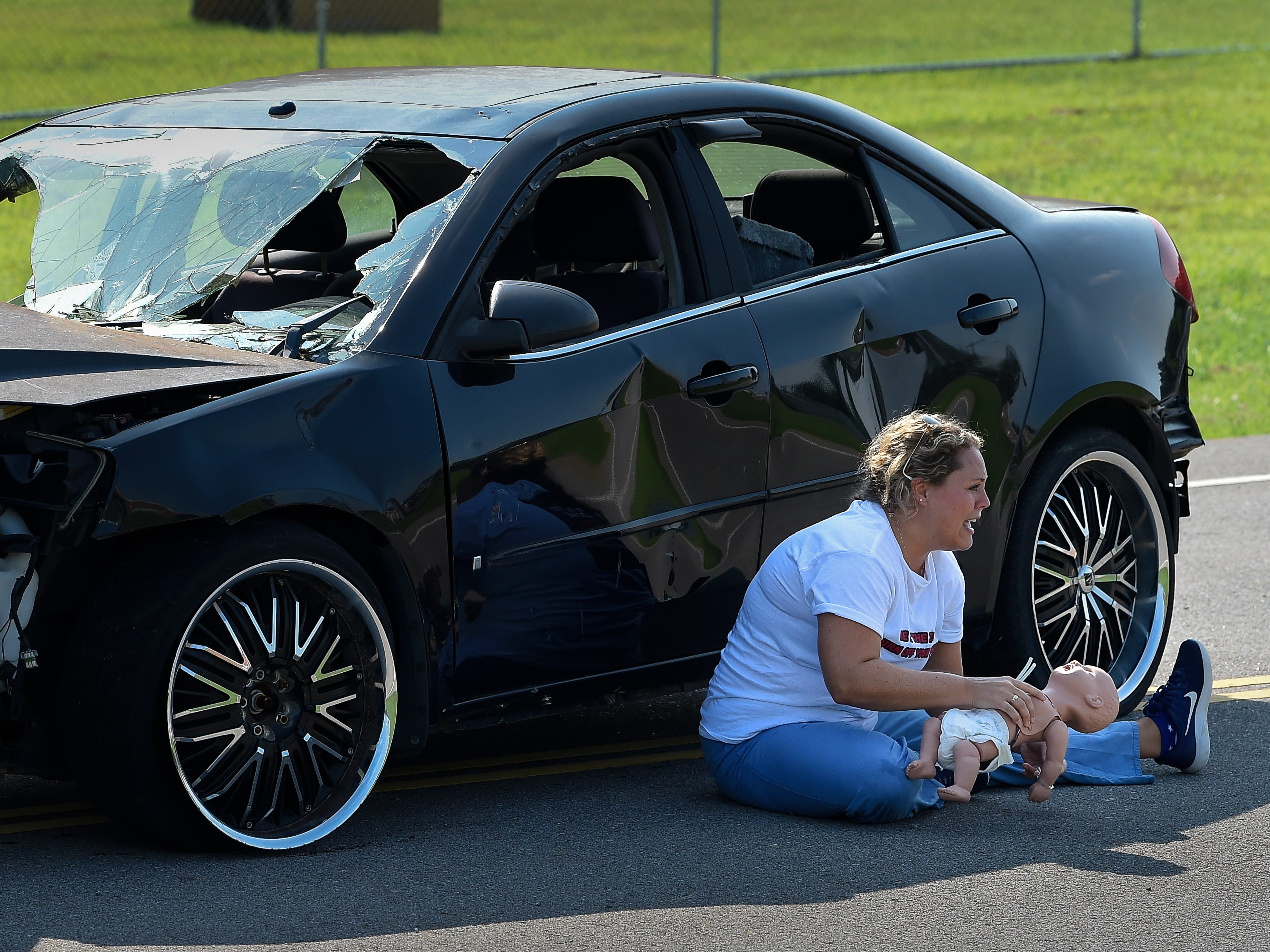 Kelsey Palladino pretends to weep as her infant is injured during a mock crash scene during a Teen Driver Education Camp held by the Tennessee Department of Safety and Homeland Security Tuesday, July 17, 2018, in Nashville, Tenn.