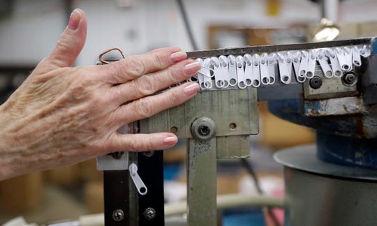 In this May 17, 2018 photo, zipper sliders travel through a machine that places them onto zipper chains at the Dunlap Industries facility in Dunlap, Tenn. The small zipper-making company is fighting to keep its pared-down staff occupied after it lost federal contracts to provide zippers for military uniforms. (AP Photo/Mark Humphrey)