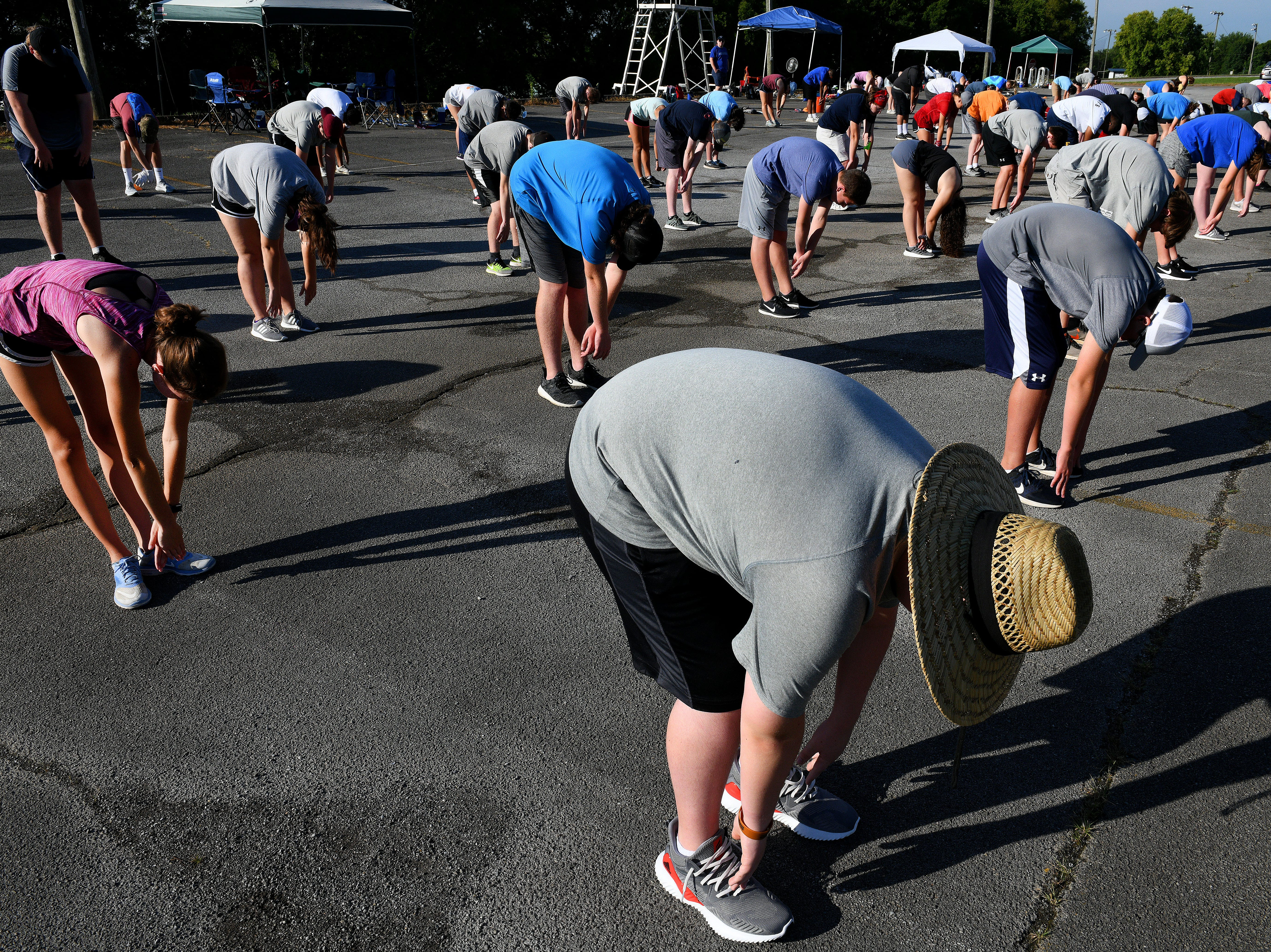 Stretching to start the day at Farragut High School band camp Wednesday, July 18, 2018 on a parking lot at the high school.