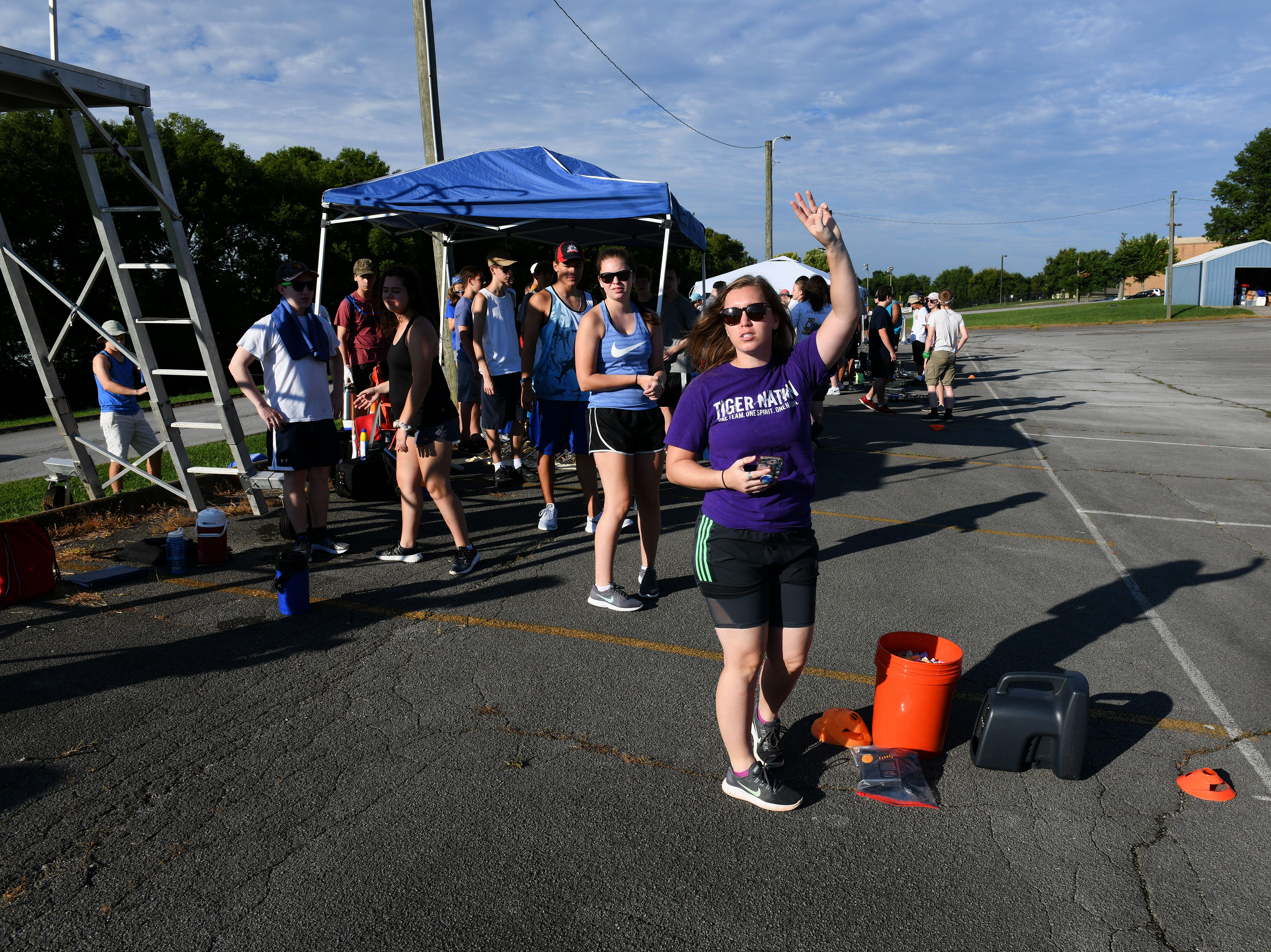Assistant director Elizabeth Gott signals 3 minutes to start Farragut High School band camp Wednesday, July 18, 2018 on a parking lot at the high school.