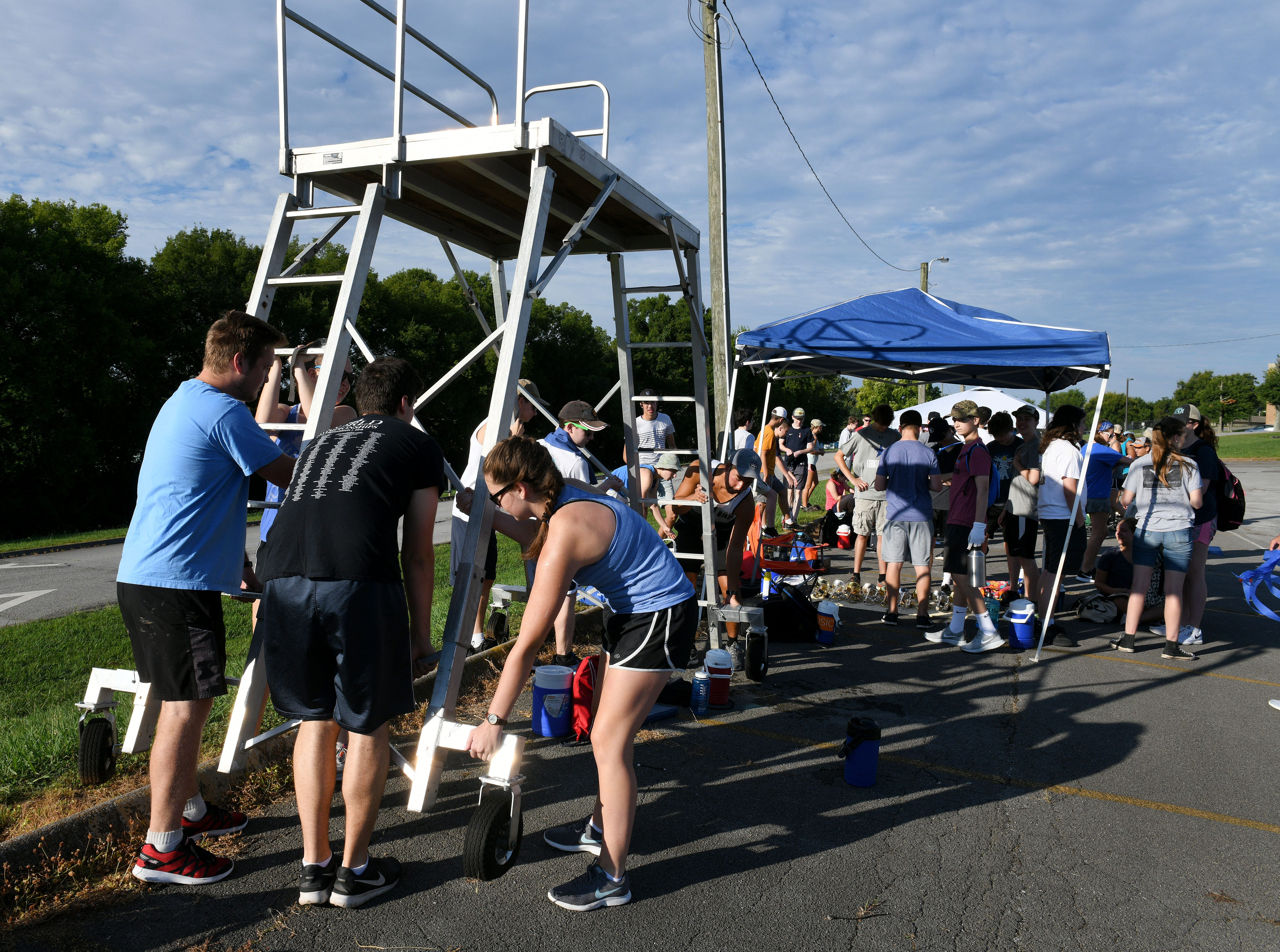Campers help move the director's stand before Farragut High School band camp Wednesday, July 18, 2018 on a parking lot at the high school.