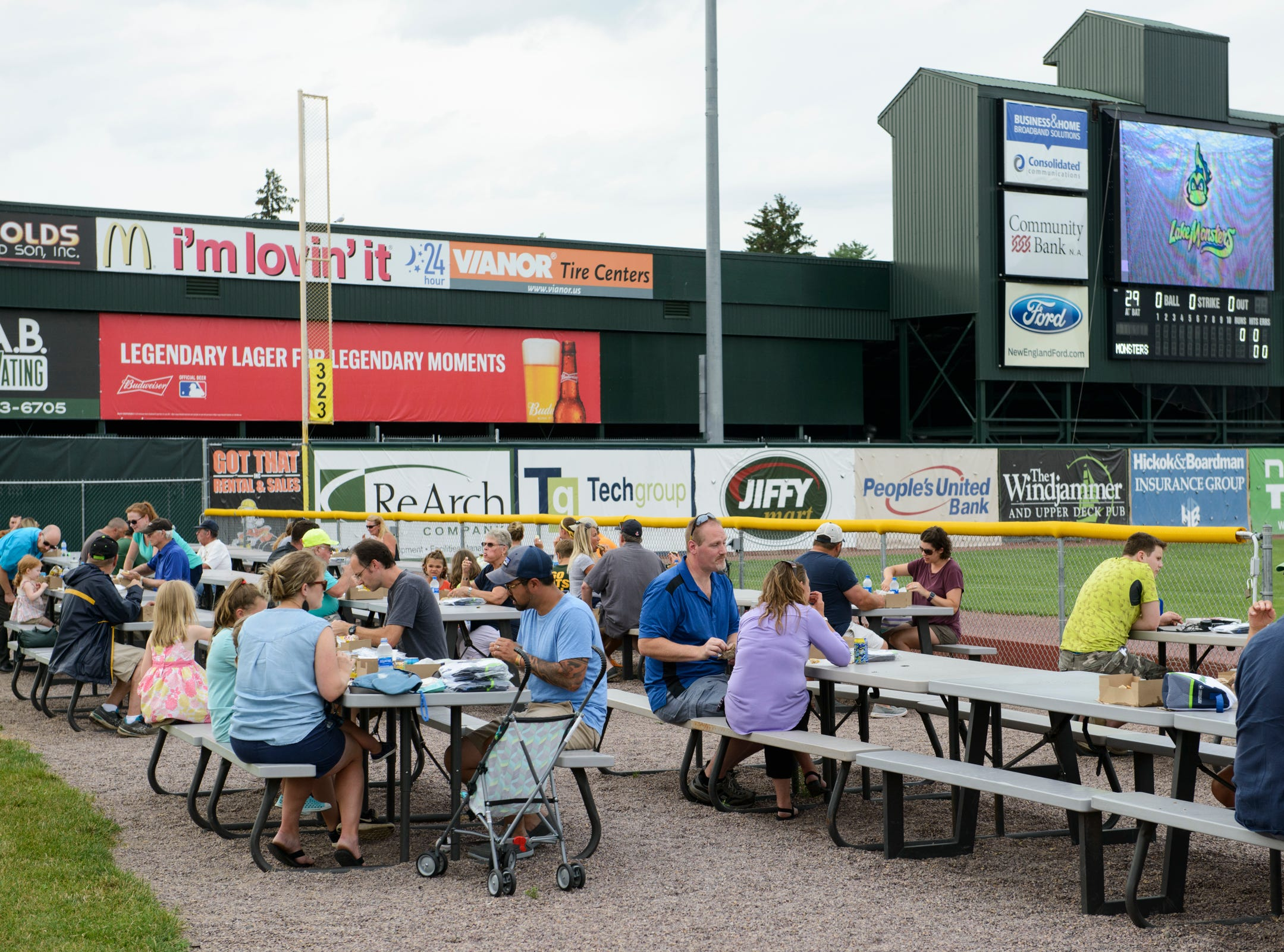 People sit and eat in the left field bleachers at the Vermont Lake Monsters game at Centennial Field on Tuesday night July 17, 2018, in Burlington.