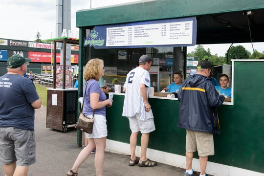 People stand in line at the food vendor at the Vermont Lake Monsters game at Centennial Field on Tuesday night, July 17, 2018, in Burlington.