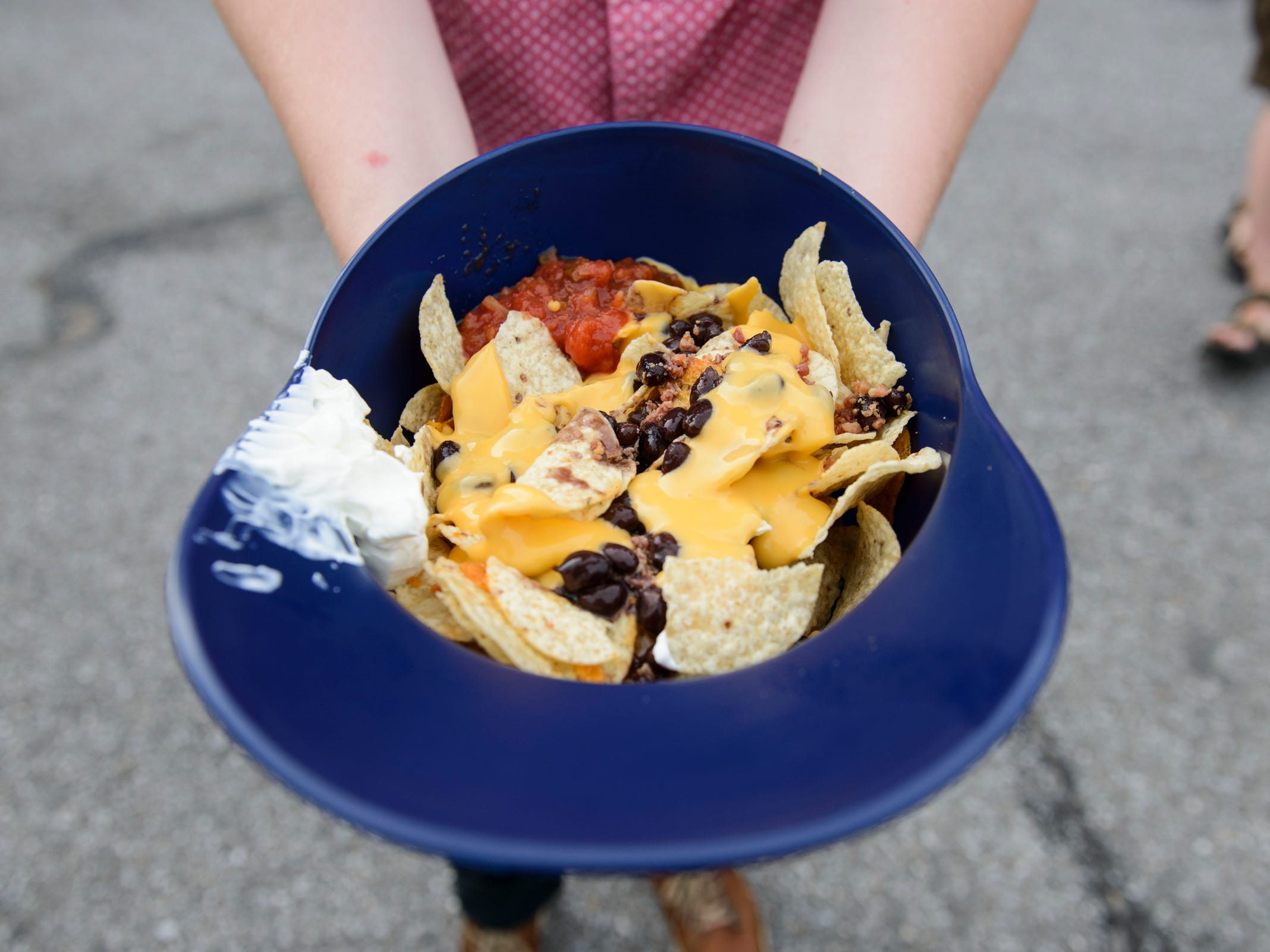 Reporter Will DiGravio shows off the Ballpark Nachos served in a full-size souvenir helmet at the Vermont Lake Monsters game at Centennial Field on Tuesday night July 17, 2018, in Burlington.