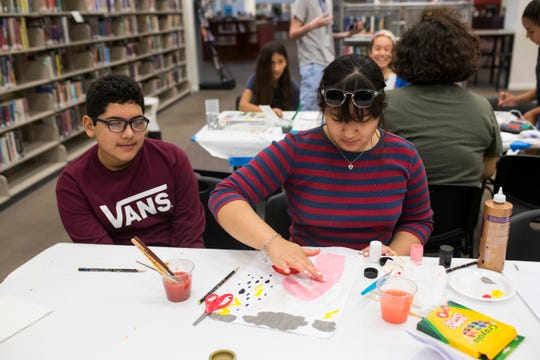 Junior Vela, 12 (left) and Gabriella Vela, 16, work on art projects during the Bad Art Afternoon on Thursday, July 19, 2018 at La Retama Central Library.