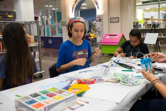 Serenah Garcia ,11 (from left), Sarina Garza, 17, and Delia De La Rosa, 11, work on projects during the Bad Art Afternoon on Thursday, July 19, 2018 at La Retama Central Library.