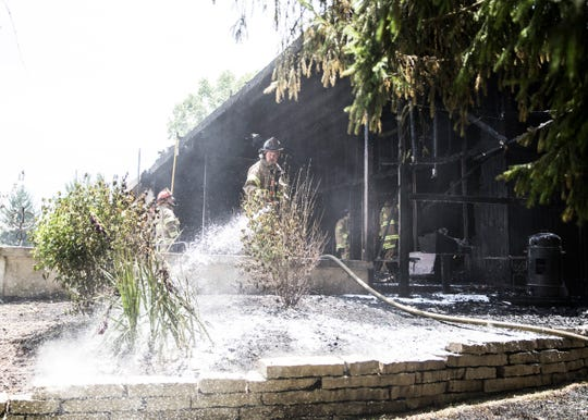 A Chillicothe firefighter hoses down the garden of a house on 47 Fruit Hill Drive to make sure any cinders or debris from the fire would not start another fire.