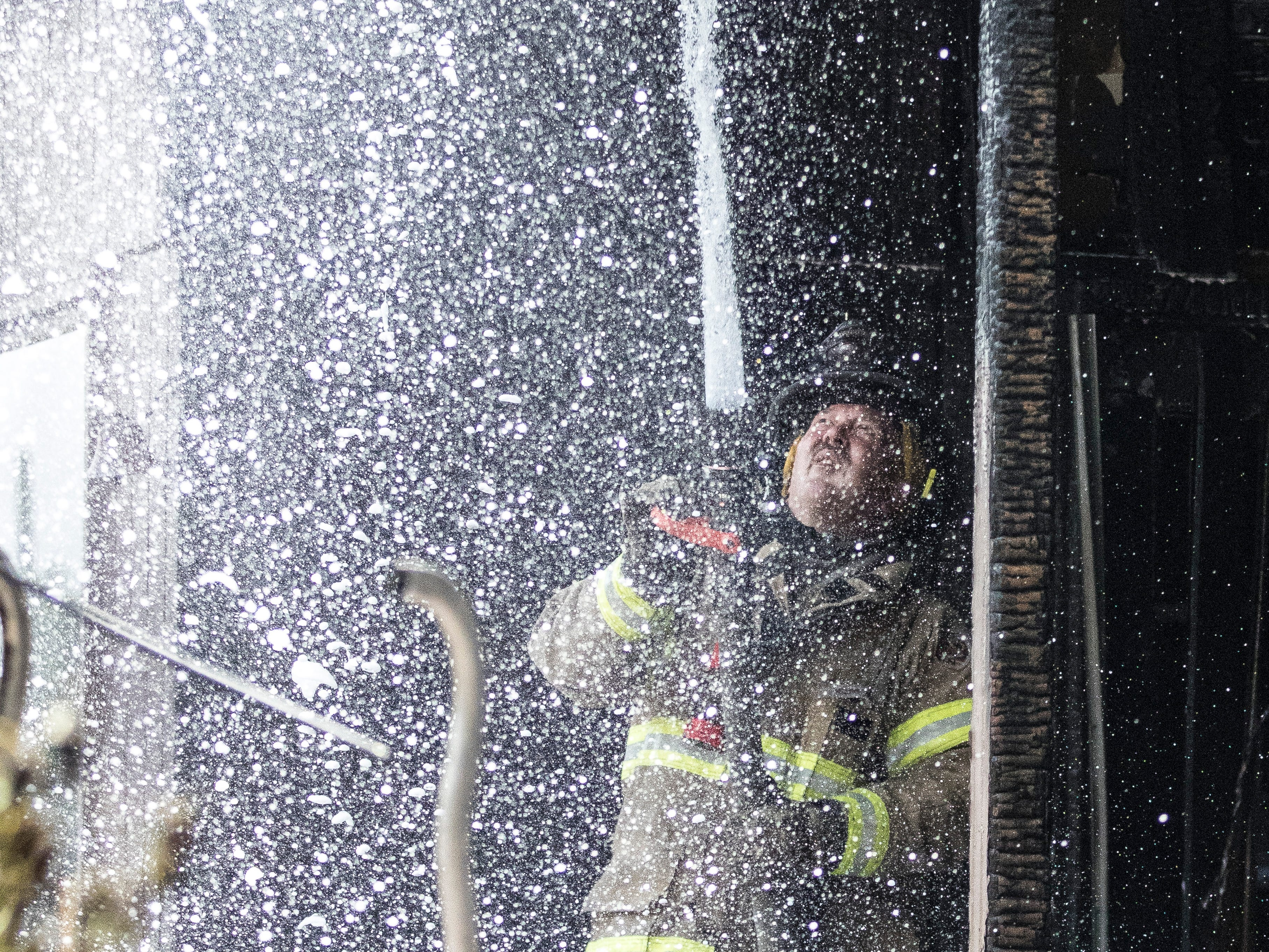 A Chillicothe firefighter hoses down the roof of a house on 47 Fruit Hill Drive to make sure all of the hot spots were taken care of Thursday afternoon.