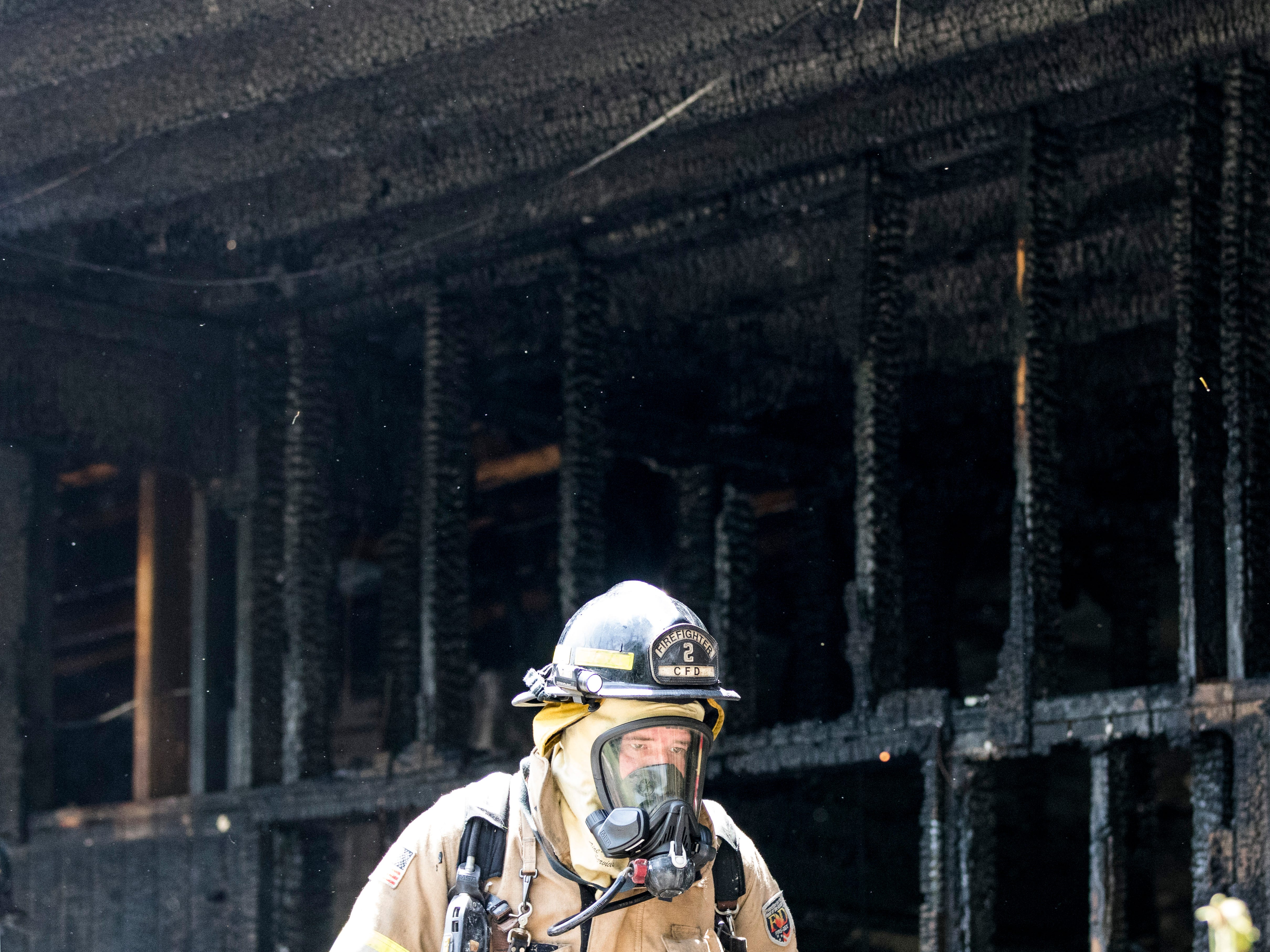 A Chillicothe firefighter wears a mask as he assesses the fire damage of a house on 47 Fruit Hill Drive Thursday afternoon in Chillicothe.