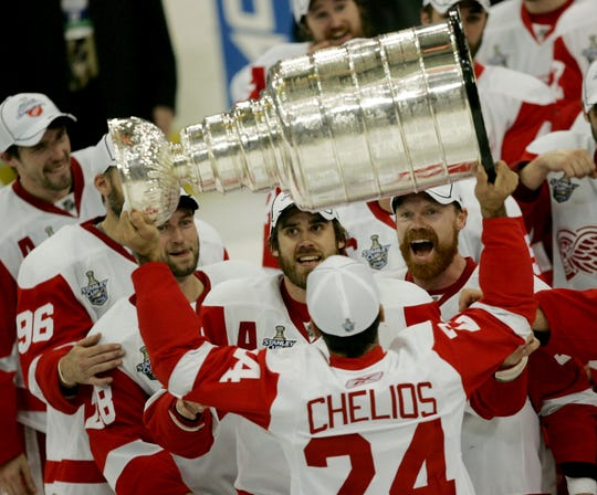 Detroit's Red Wings Chris Chelios hands the Stanley Cup off to Henrik Zetterberg after their 3-2 victory in game 6 of the Stanley Cup Finals Wednesday, June 4, 2008 at the Mellon Arena in Pittsburgh, PA.