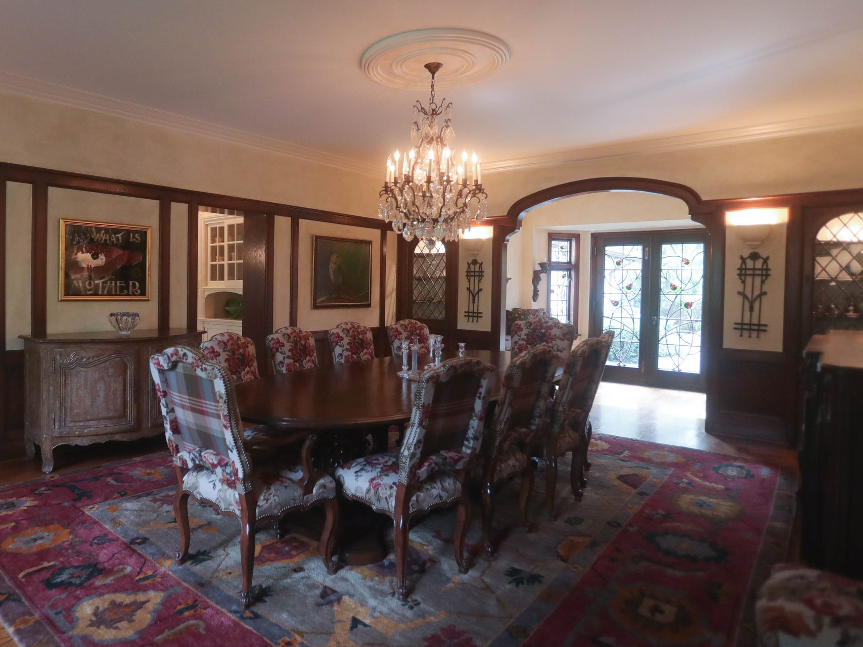The party-size dining room has built-in corner cabinets with diamond-shaped leaded glass. At the far back, an alcove has built-in seats. Its French doors and side windows carry gradeful [ stained glass images of acorns.