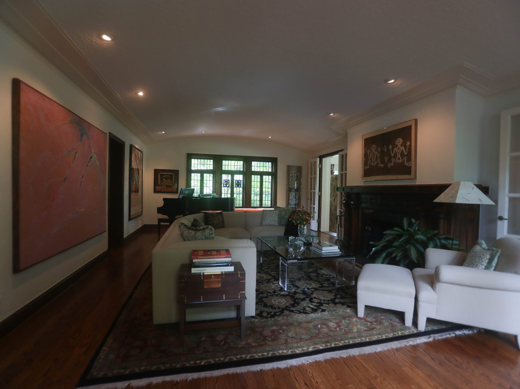 The long, formal living room has a wide, carved wood fireplace, a barrel ceiling and  leaded glass windows. The French doors at right lead to the dining room.
