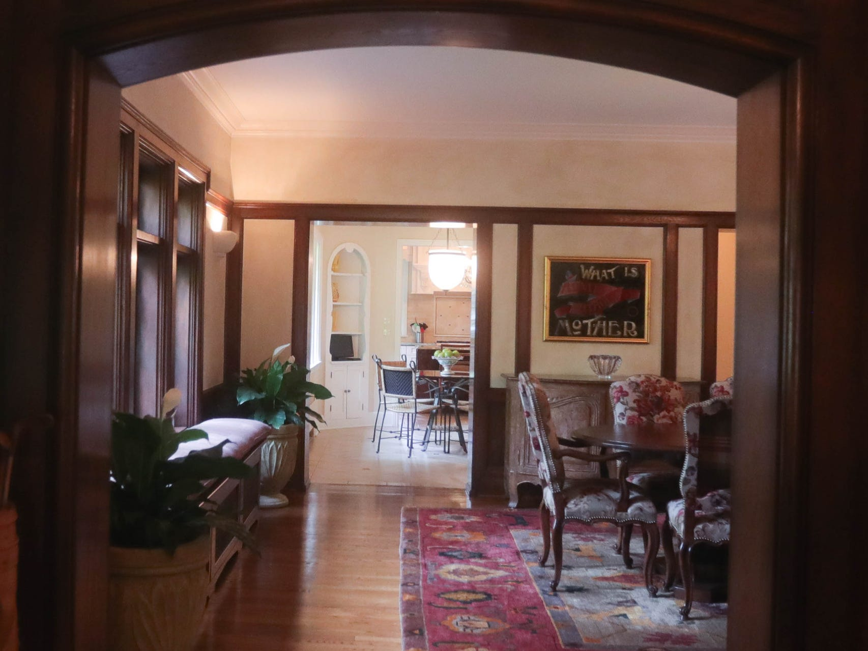 The long view from the entry foyer goes through the living room, then the dining room, the breakfast room to the kitchen. Carved oak woodwork is one of the house's assets.