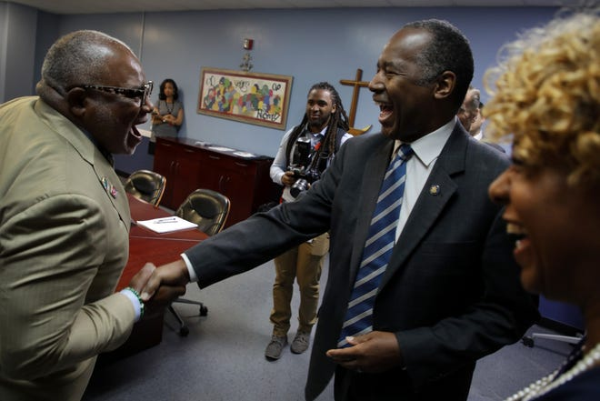 Secretary of Housing and Urban Development Ben Carson, greets Mariners Inn board of Trustee member Carl Bentley, left and COO Carina Jackson, right, during a visit of the treatment center and shelter for the homeless in Detroit on Thursday, July 19, 2018.