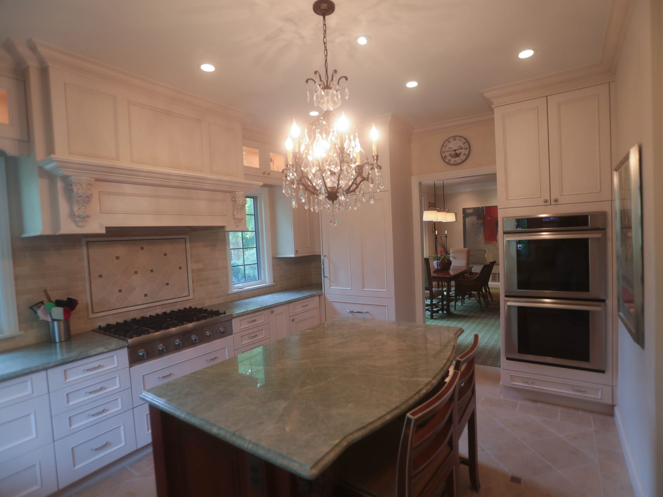 The kitchen was enlarged and remodeled with glazed antique white cabinets, granite counters and a stone tile floor.