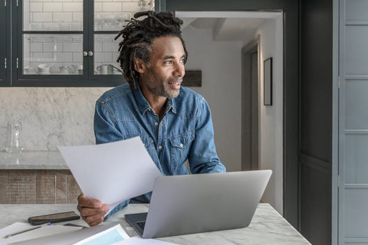 Confident Businessman In His 50s Working From Home With Laptop And Paperwork