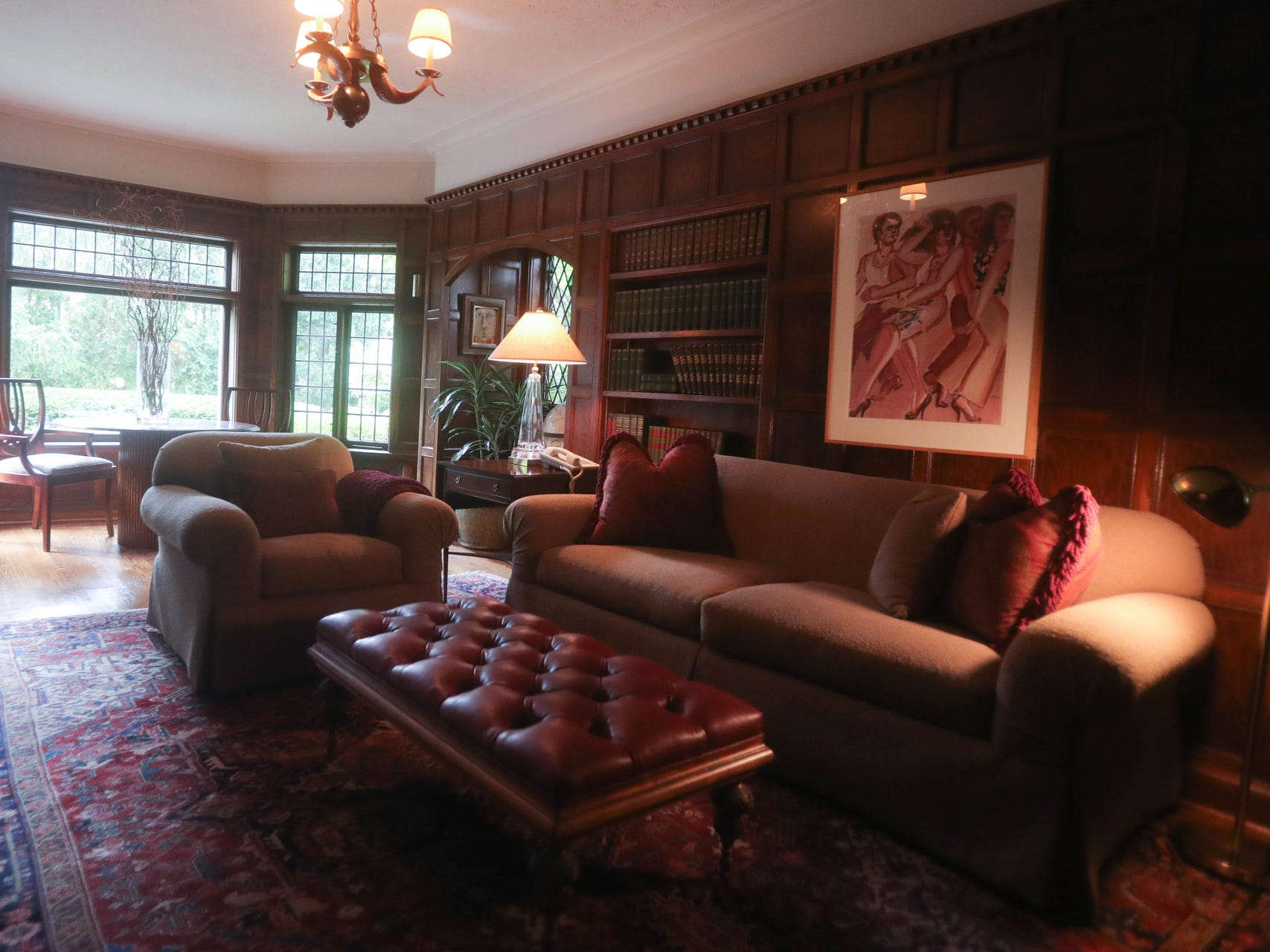 The library is wrapped in carved paneling with a leaded glass bay at the end. The paneling hides a secret compartment.