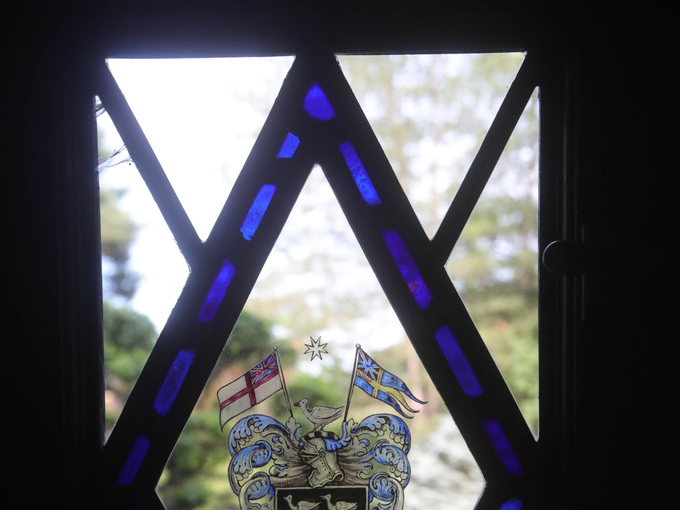 Personalized stained glass through the house include this family crest with symbols  from the Union Jack and Swedish flags.