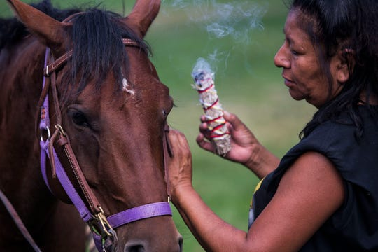 LakotaRide 2018 board member Aurelia Wilson blesses the horse that her daughter is riding with burning sage to ensure a safe ride before heading North to Fort Collins on Thursday, July 19, 2018, at Namaqua Park in Loveland, Colo.