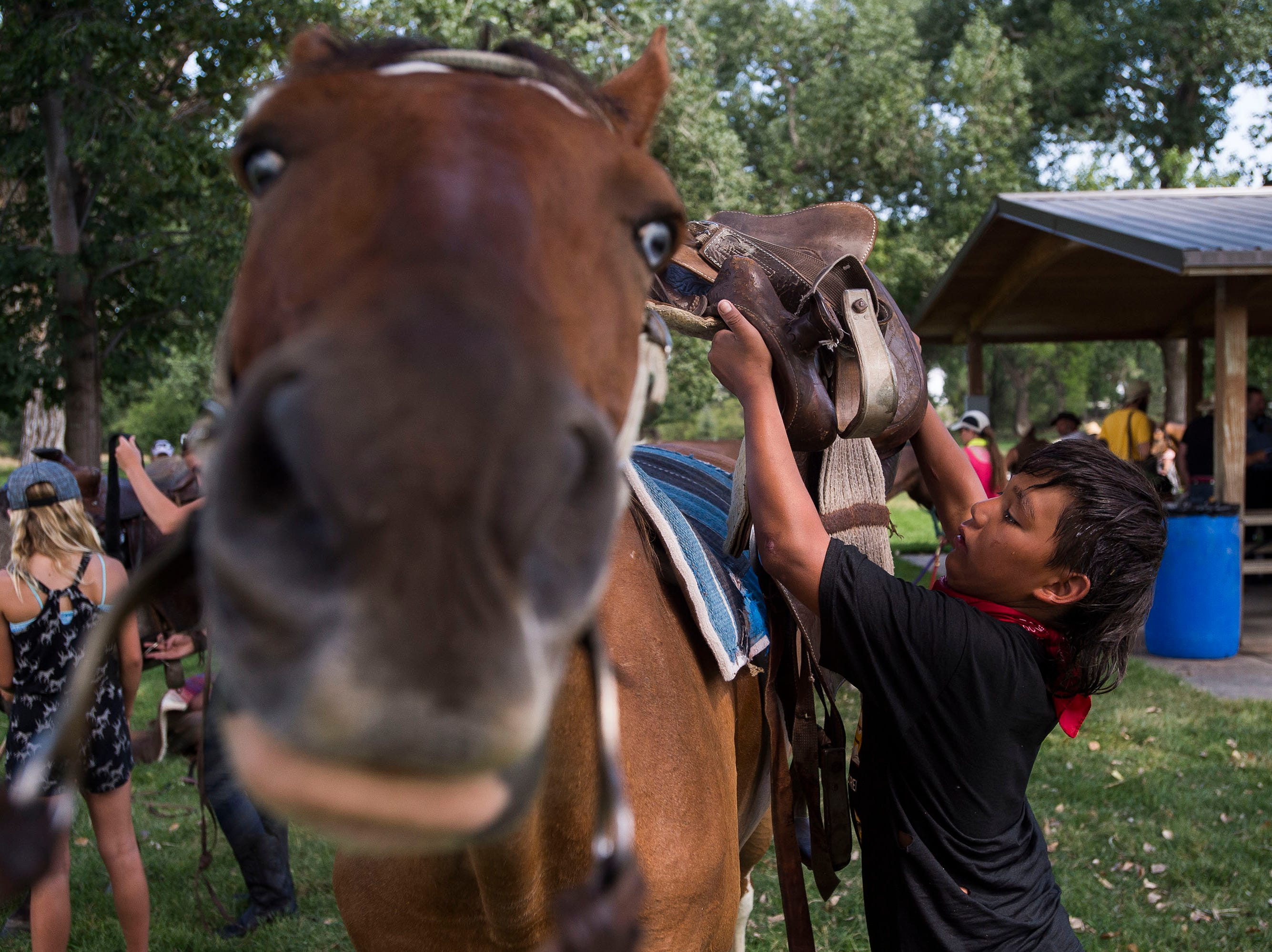 Thomas Belt, from the Pine Ridge Indian Reservation, saddles up his horse, Bandoo, on Thursday, July 19, 2018, at Namaqua Park in Loveland, Colo, before heading North to Fort Collins.