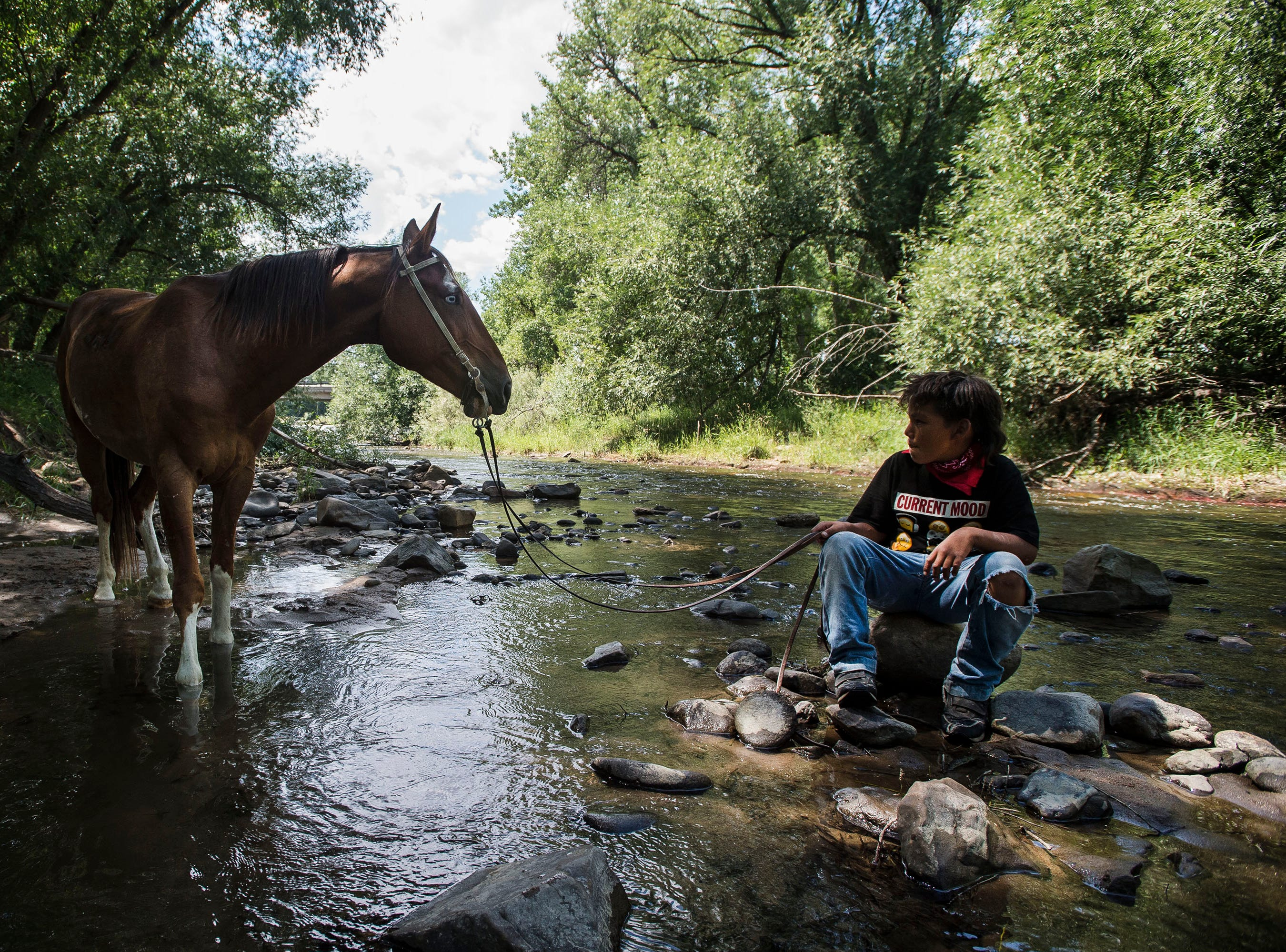 Thomas Belt, from the Pine Ridge Indian Reservation, lets his horse Bandoo take a rest in the Big Thompson River after riding into town on Thursday, July 19, 2018, at Namaqua Park in Loveland, Colo, before heading North to Fort Collins.