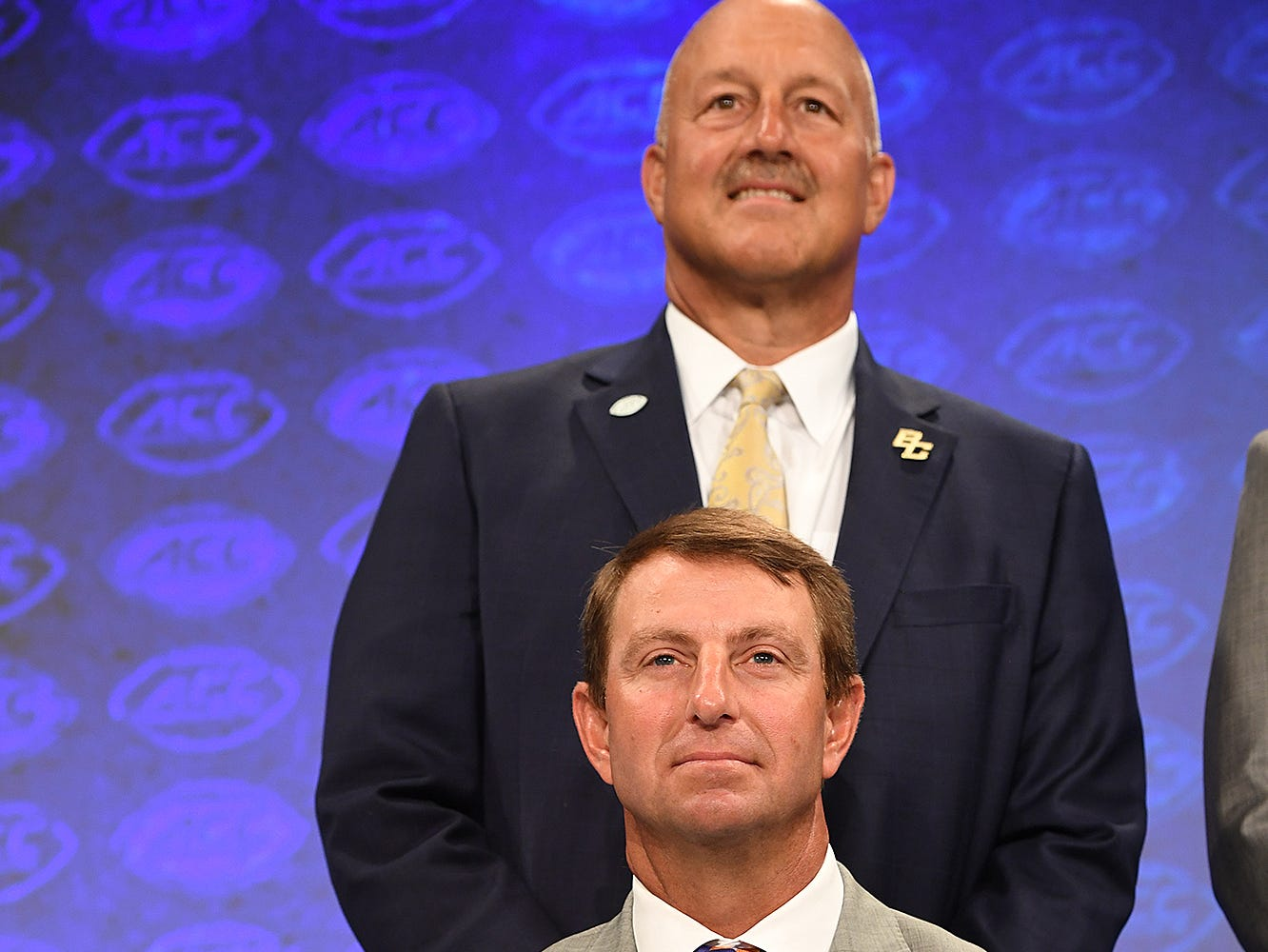 Clemson head coach Dabo Swinney, front, with Boston College head coach Steve Addazio during the Atlantic Division group photo at the ACC Football Kickoff in Charlotte, N.C., Thursday, July 19, 2018.