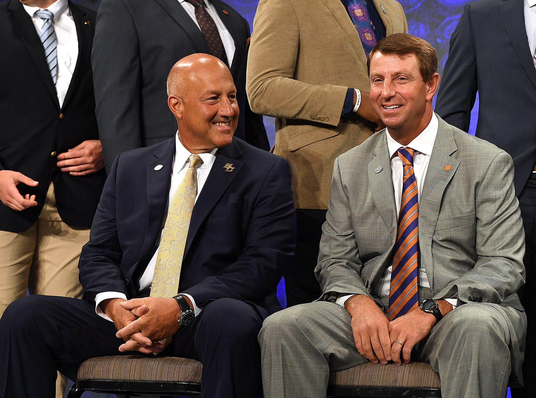 Clemson head coach Dabo Swinney, right, sits with Boston College head coach Steve Addazio while waiting on the Atlantic Division group photo at the ACC Football Kickoff in Charlotte, N.C., Thursday, July 19, 2018.
