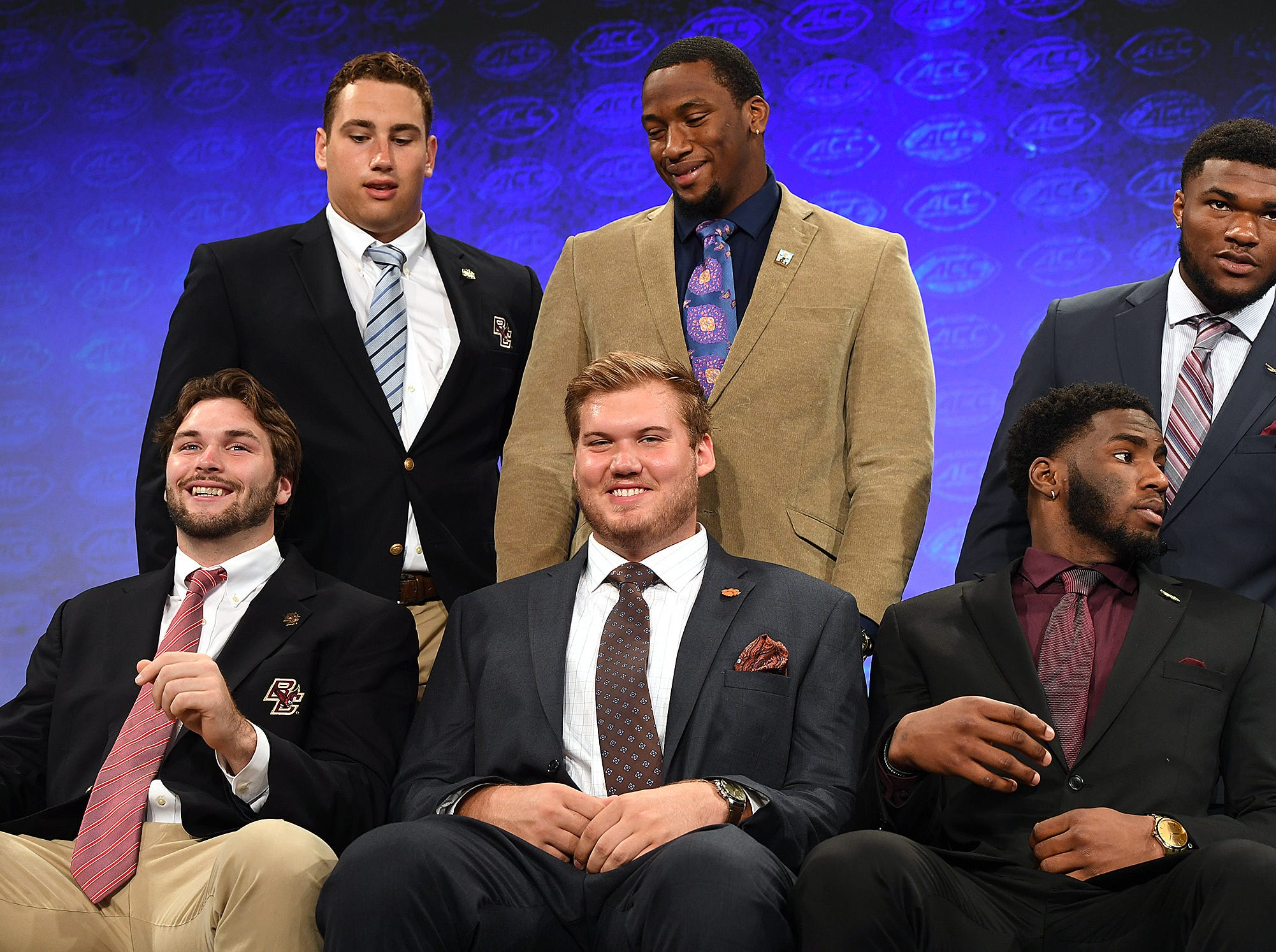 Clemson's Mitch Hyatt, front center, and Clean Ferrell wait on the Atlantic Division group photo at the ACC Football Kickoff in Charlotte, N.C., Thursday, July 19, 2018.