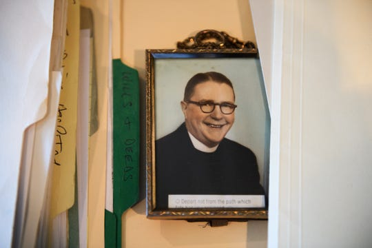 A photograph of Rev. Thomas Sullivan sits in between folders full of documents Jim Graham gathered during his investigation to prove that he is the son of the catholic preacher.