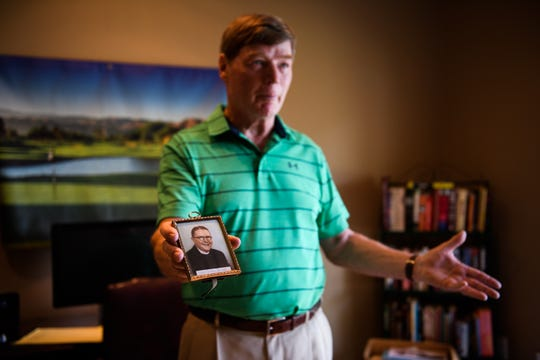 Jim Graham holds out a photograph of the Rev. Thomas Sullivan, who was recently proven through DNA testing to be Graham's father, at his home on Tuesday, July 18, 2018.