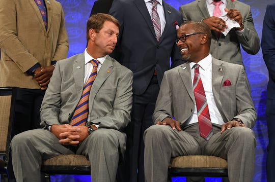 Clemson head coach Dabo Swinney, left, sits with Florida State head coach Willie Taggart while waiting on the Atlantic Division group photo at the ACC Football Kickoff in Charlotte, N.C., Thursday, July 19, 2018.