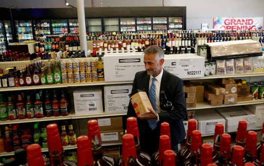Jim Canepa, superintendent of the Ohio Division of Liquor Control, looks for items to purchase Thursday, July 19, 2018, at The Pit Stop in Lancaster. Canepa made the first purchase at the new state liquor agency.
