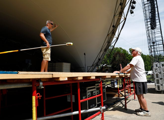 Max McGee, right, listens as a fellow Lancaster Festival volunteer explains how a new cleaning process is working on the inside of the Ohio University Lancaster Wendel Concert Stage performance shell Thursday morning, July 19, 2018, in Lancaster. McGee has been volunteering with the festival since it began. He and a few other volunteers spend a month camped at Ohio University Lancaster performance space to prepare it for the festival.