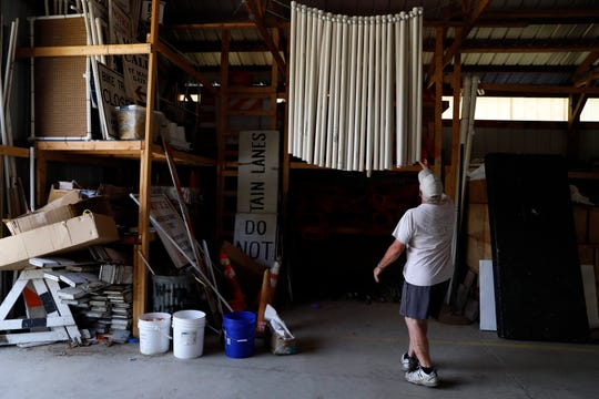 """Max McGee looks through parking lot letter signs that are stored in a barn he affectionately calls """"Pandora's Box"""" Thursday, July 19, 2018, in Lancaster. The barn houses all of the materials to put together and mark the Ohio University Wendel Concert Stage and the surrounding parking lots."""